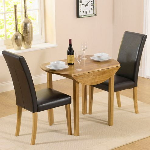 oak round drop leaf table and 2 black chairs from our dining table